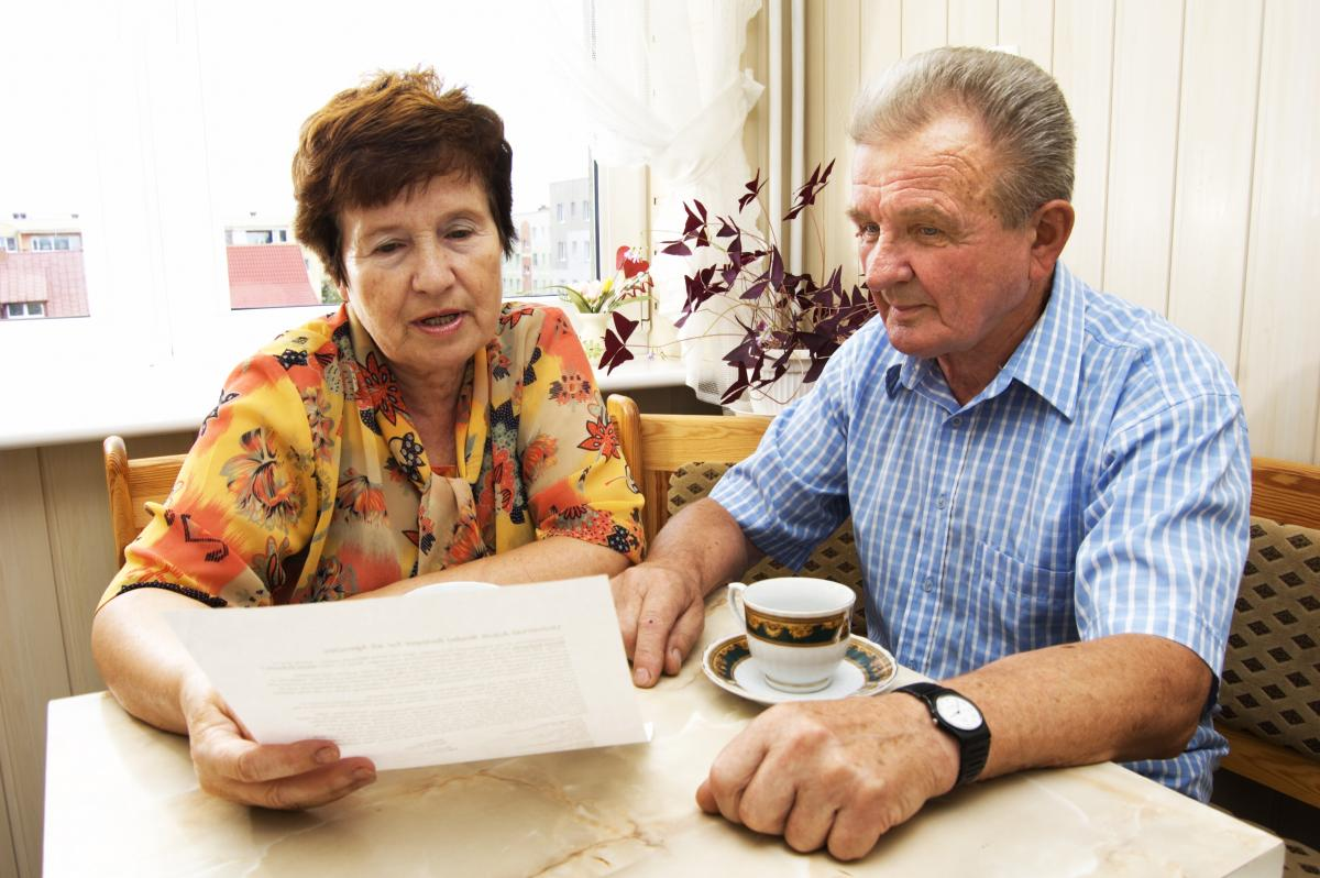 A retired couple looking over paperwork.