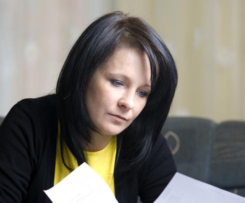 A woman looking at bills at a table.