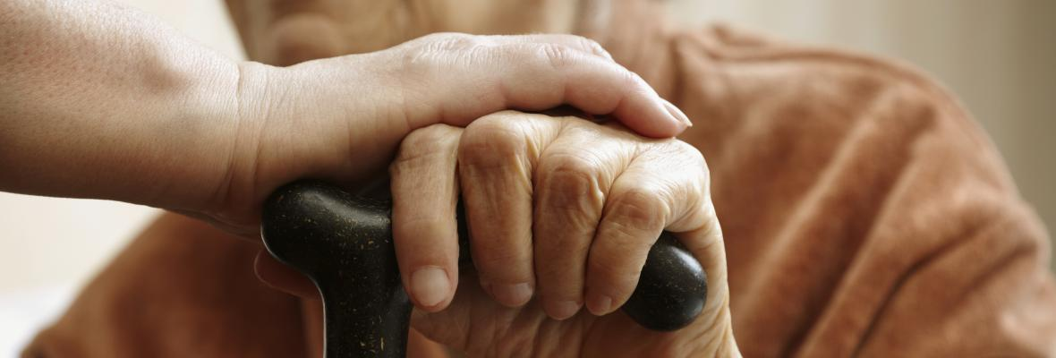 A young hand comforts and older hand