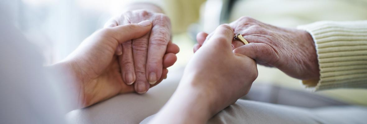 A younger person holding the hands of an older person.