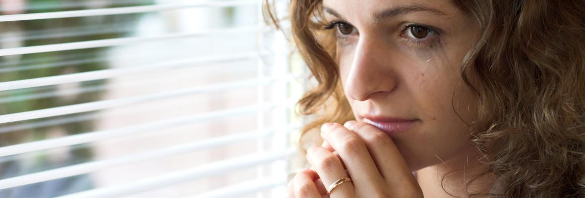 A tearful young woman looking out of window anxiously.