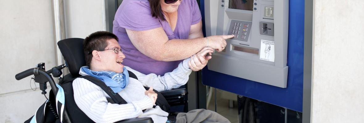 A young man in wheelchair with his carer, being helped to use an cash machine.