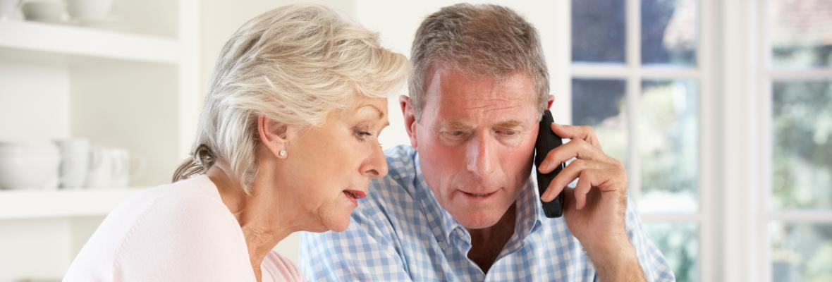 An older man and a woman speaking to someone on the phone.
