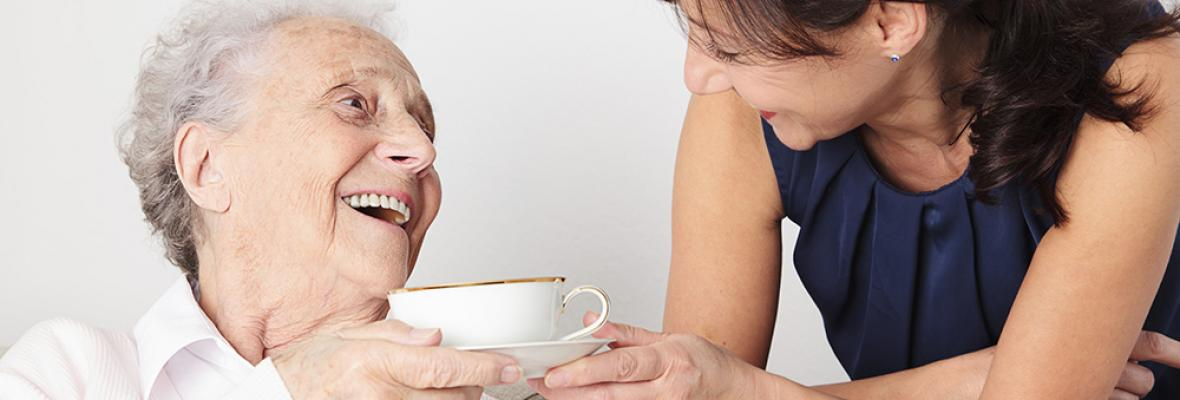A younger woman passes a cup of tea being handed to an elderly lady.