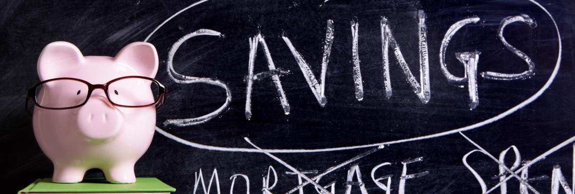"""Savings"" written on a chalkboard with a piggybank in front of it."