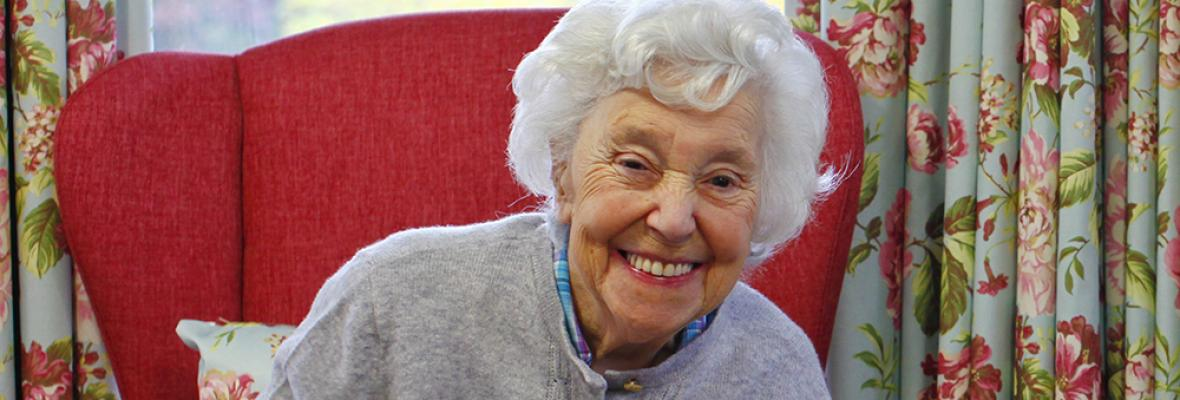 A older lady sitting smiling in a bright red chair - photo from Dementia UK