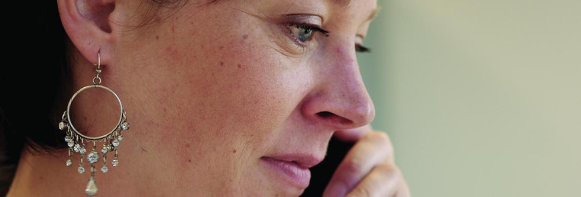 A woman talks on a phone.