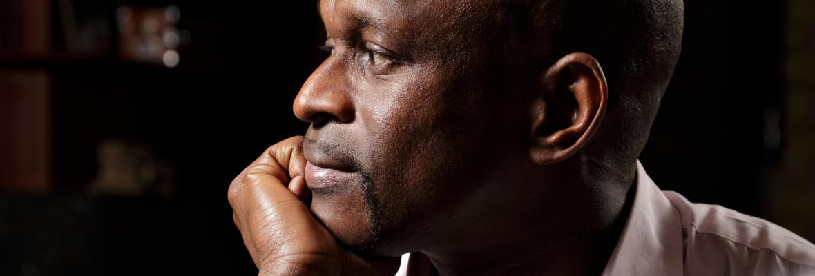 A man rests his head on his hand, looking pensively to the right.