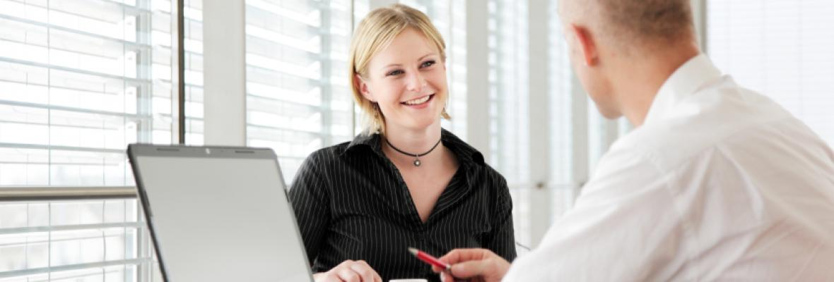 A woman smiles and talks to a man in white shirt sat by a computer.
