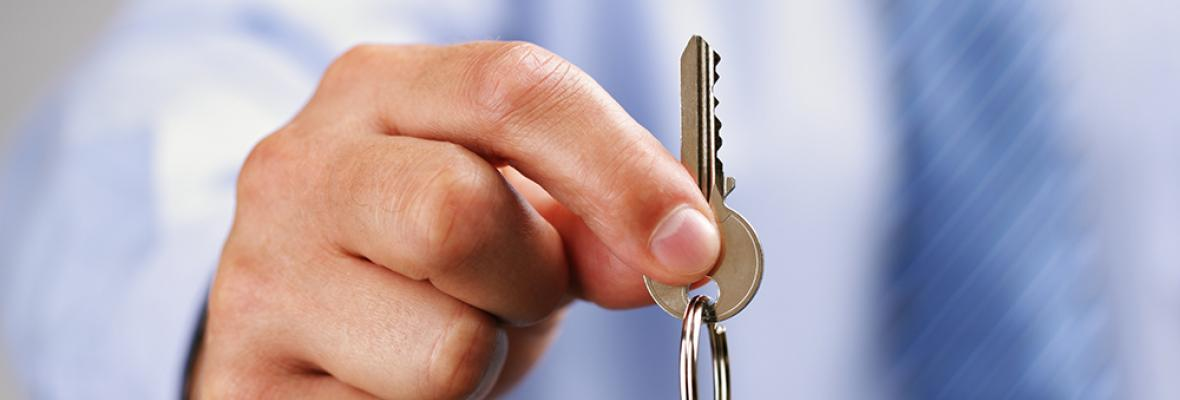 A man holds out a key to a house.