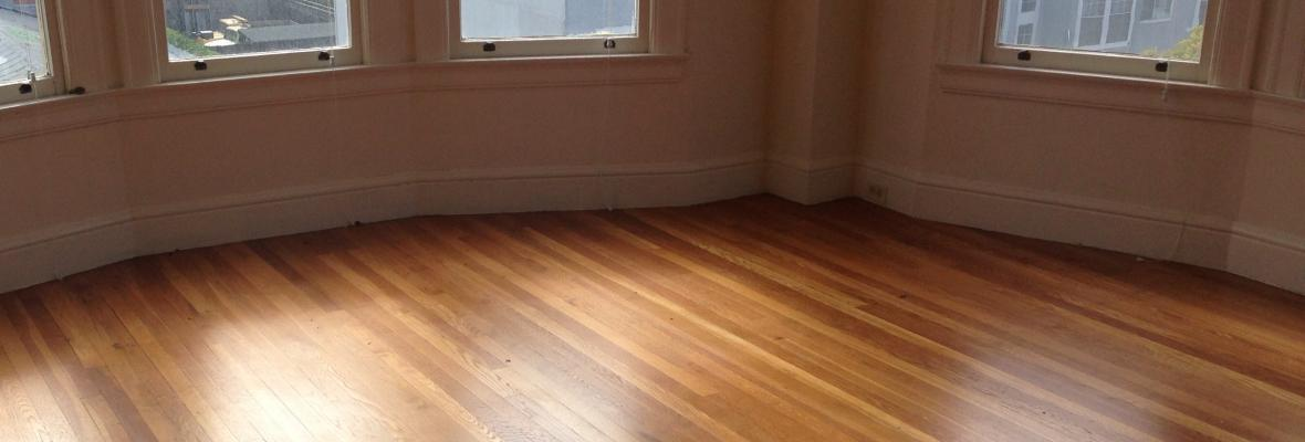 Bare room with wooden flooring.