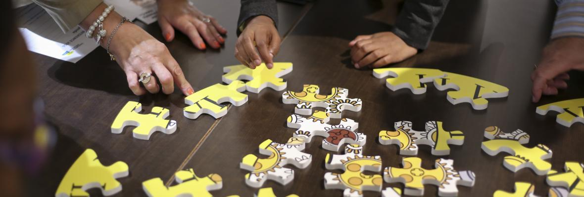 People putting together a jigsaw in a group