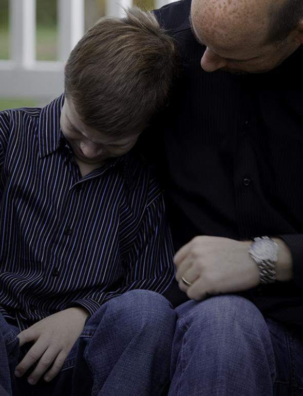 Father consoling his son, sitting outside.