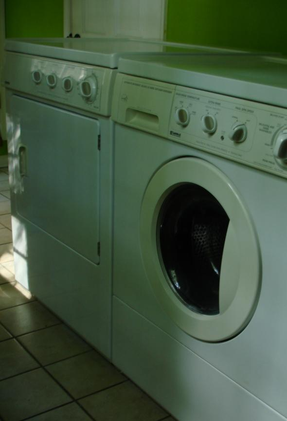 A washing machine and tumble dryer next to one another in a dark utility cupboard