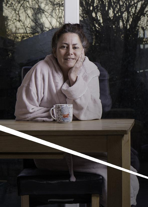 A middle-aged woman sitting at her table in her dressing gown, smiling to camera.