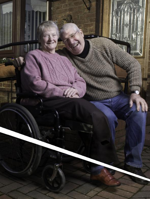 An older couple sit, smiling.