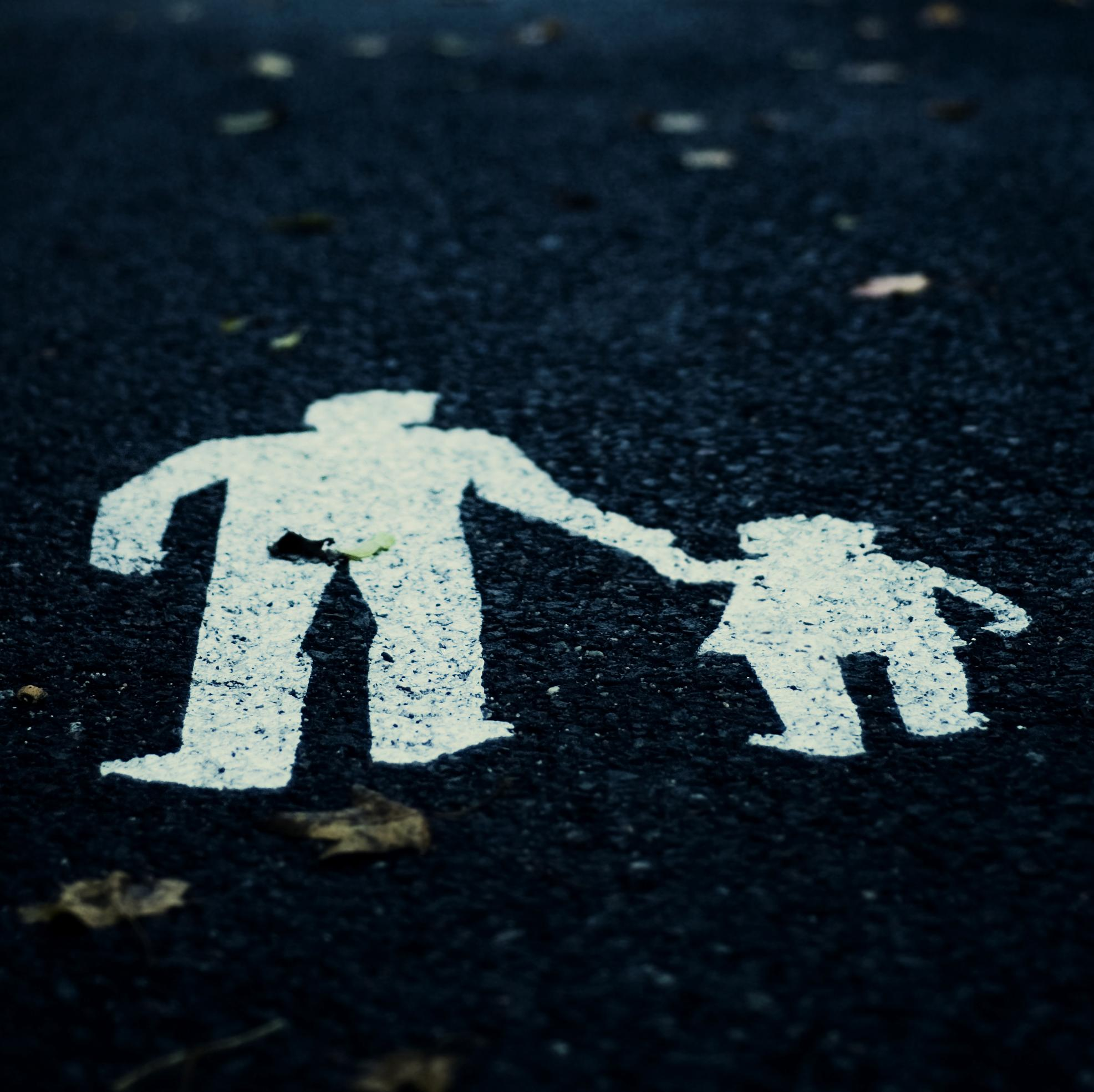 Painting on a road of adult and child holding hands.