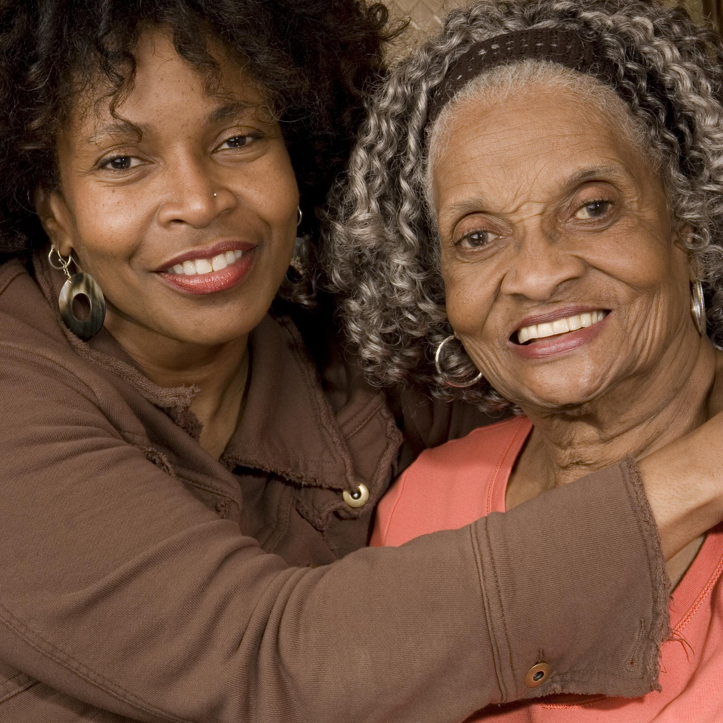 Two black women, a younger woman holds her mother in an embrace.