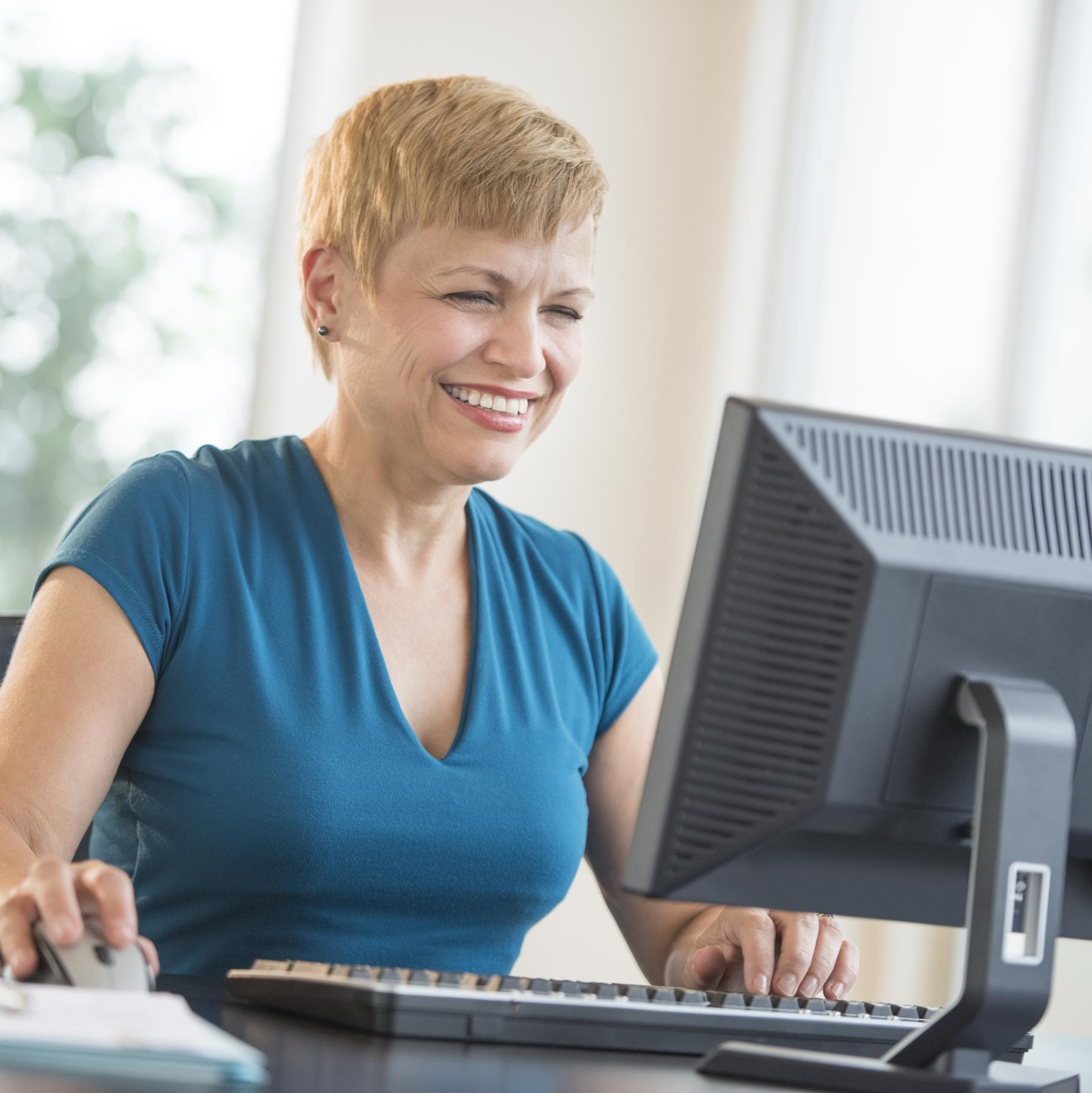 A smiling woman in blue uses a computer.