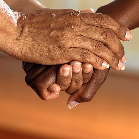 A closeup of two people holding hands.