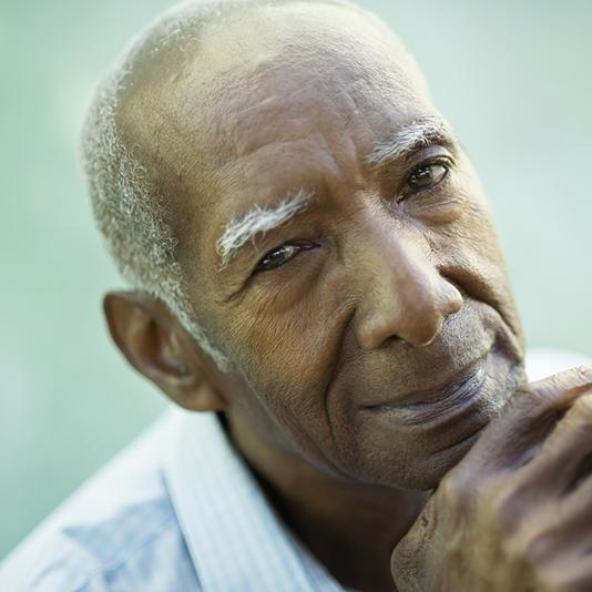 An old man rests his head against his interlocked hands, smiling.