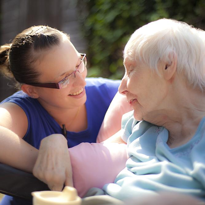 An old woman looks to the side at her younger carer.