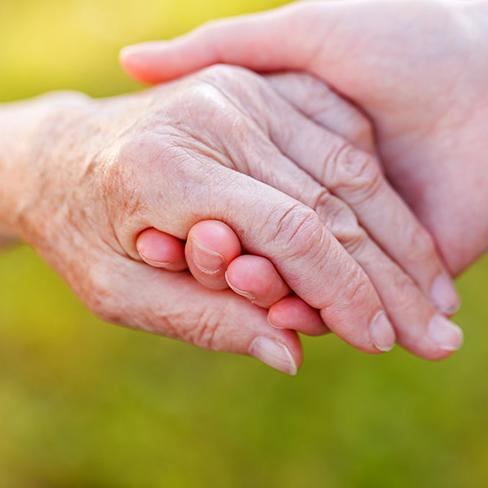 A younger person helps an older person up, taking their hand.