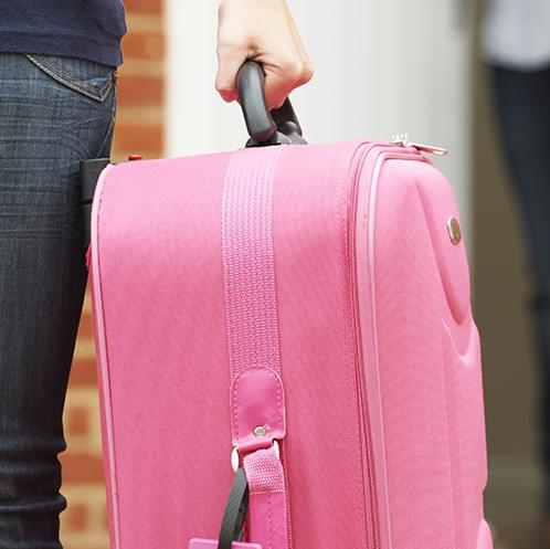 A woman leaving a house with a pink suitcase, watched by a man in the door.