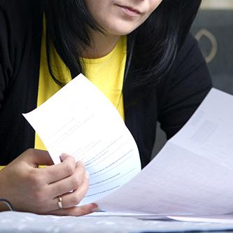 A woman leafing through sheets of paper.