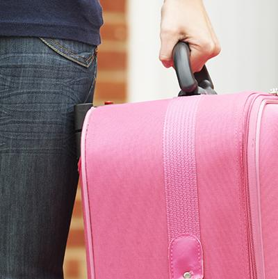 A woman walks away from a house, carrying a pink suitcase, watched by a man in the doorway.