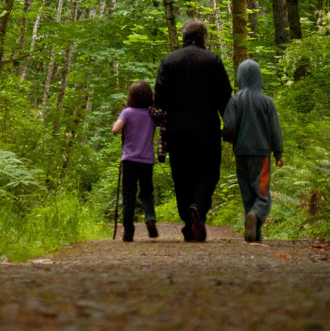 A father and two children walking through the woods.