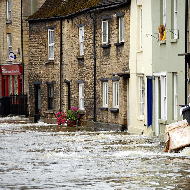 A row of white and brown terraced houses in a flooded street, with a woman in a yellow jumper leaning out.