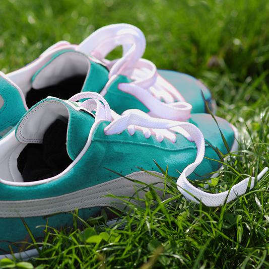 A close-up of blue running shoes on grass.