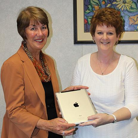 A woman hands an iPad to another woman