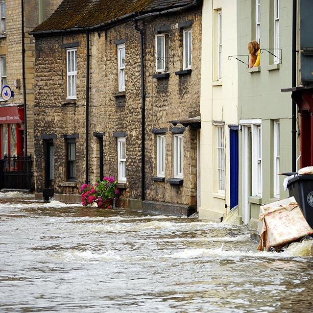 Water floods a street as a woman looks forlorn from the top window of her house