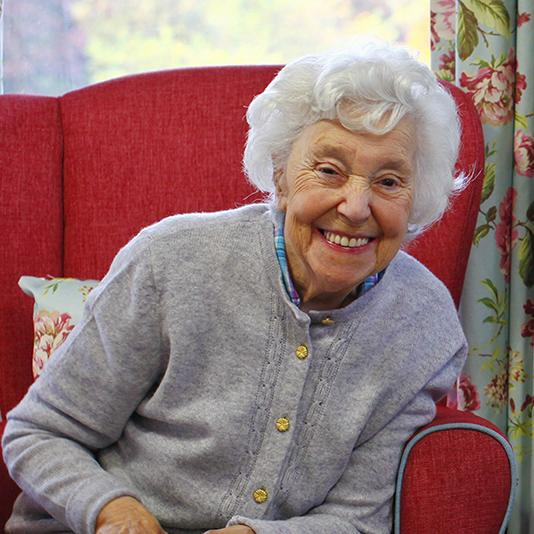 Elderly lady smiling whilst sitting in a red chair.