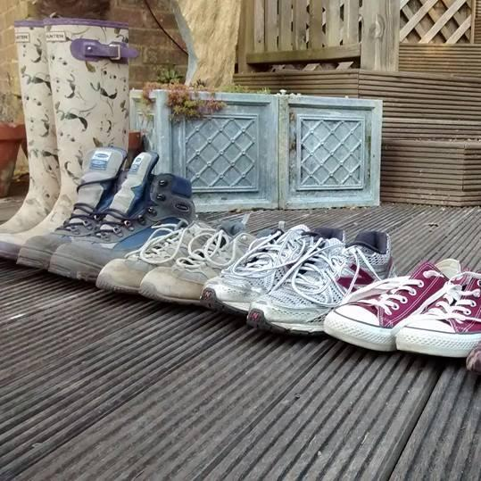A row of assorted footwear on garden decking