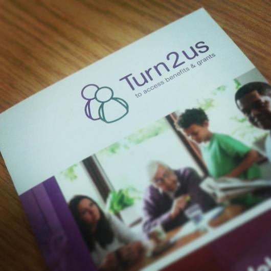 A close-up of a Turn2Us brochure placed on a table