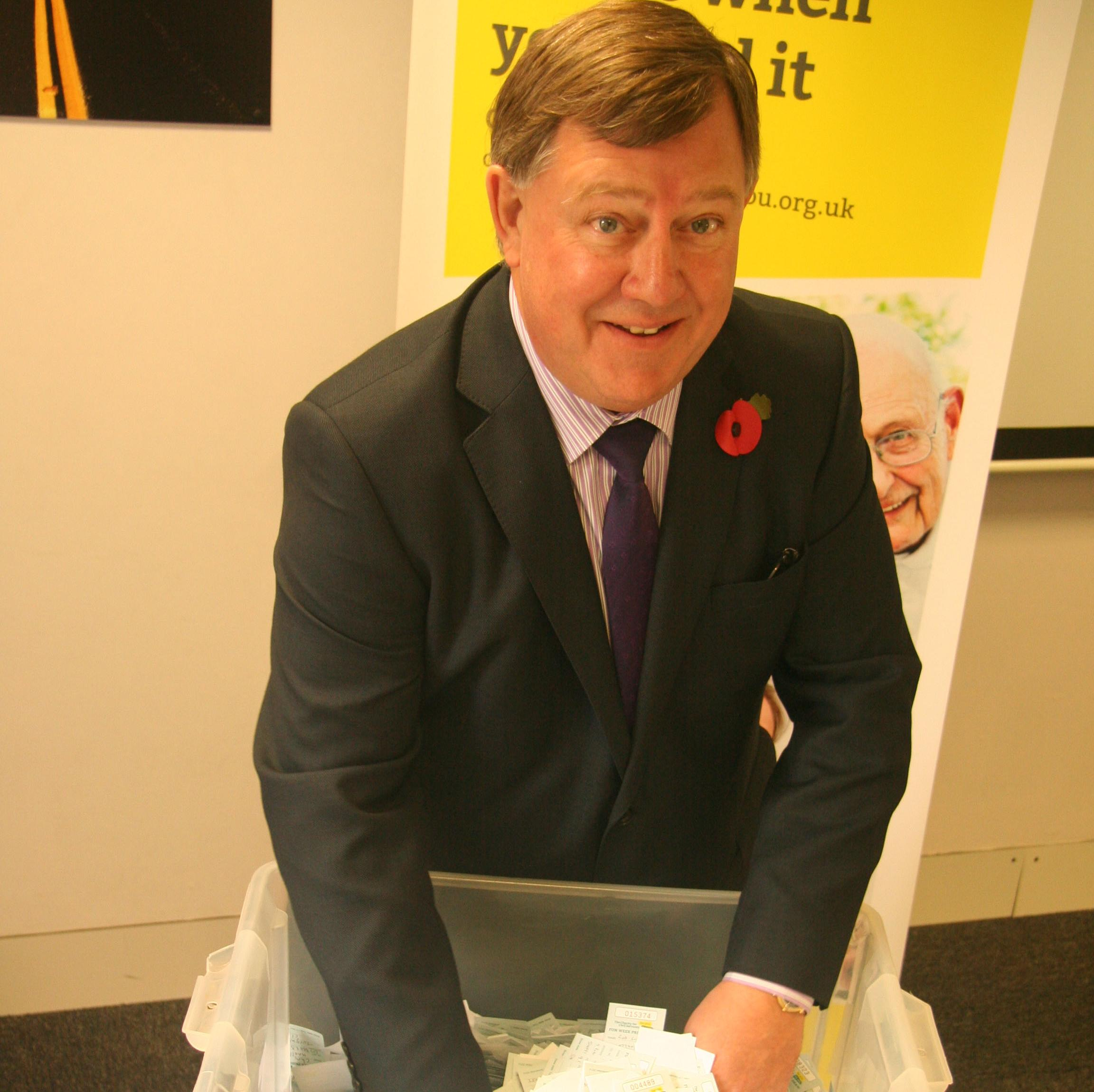 Kevin Holliday CEO pulling prize draw tickets for the Charity for Civil Servants