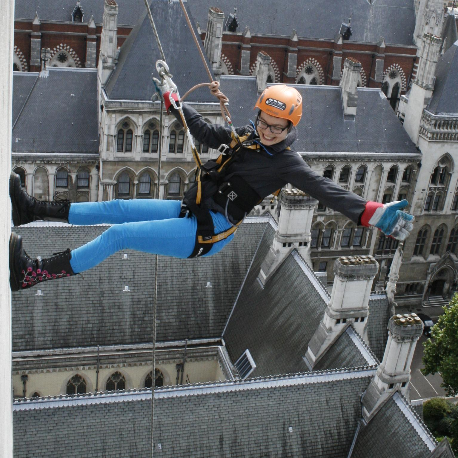 A young woman abseiling down a building in London.