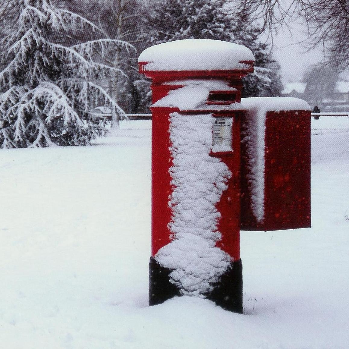 A snowy scene with a red postbox.