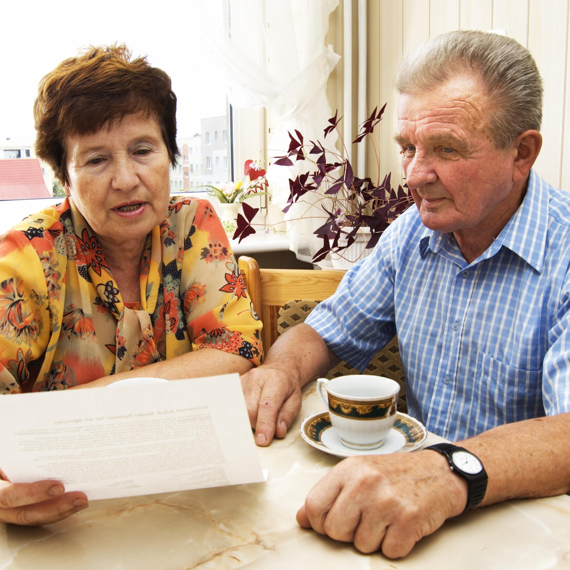 A retired couple looking over paperwork at a table.