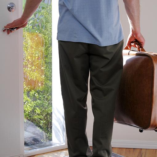 A man leaving a house, with a suitcase.