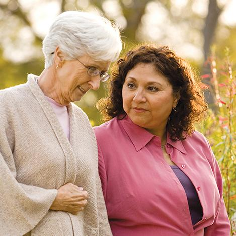 A older woman walking with another woman through a park.
